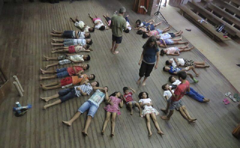 Crianças deitadas em roda no chão